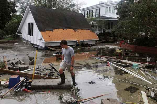Resident_Joseph_Eudi_looks_at_flood_debris_and_storm_damage